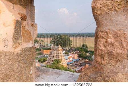Chettinad India - October 16 2013: View out of Thirumayam Fort through one battlements opening upon village and temple gopuram.