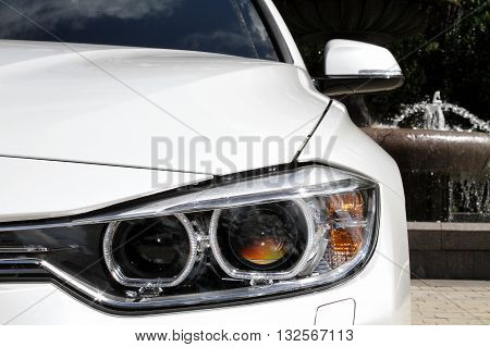 Headlights of white car closeup stock photo