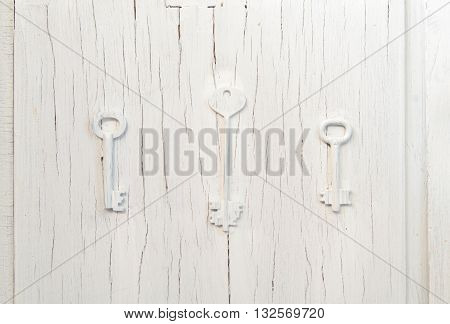 Three keys trendy decor on an old gray cracked door vintage abstract design cluse-up background. Choice of path concern