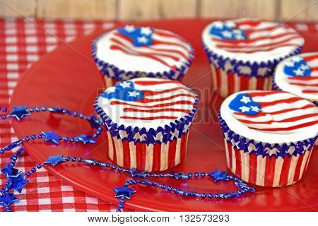 American flag cupcake icing on red plate with blue star necklace.