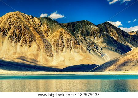 Beautiful Mountains and Pangong tso (Lake). It is a huge lake in Ladakh extends from India to Tibet. Leh Ladakh Jammu and Kashmir India. Himalayan mountains in background. Colourful stock image.