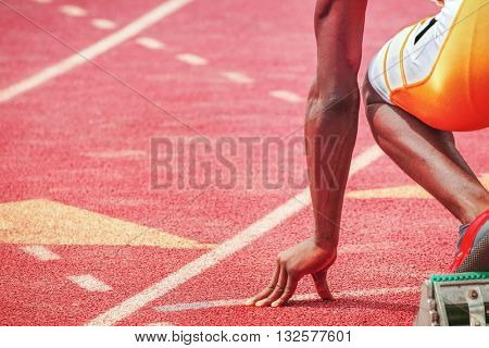 Runners fingers on the starting line, ready for the start of a track and field race