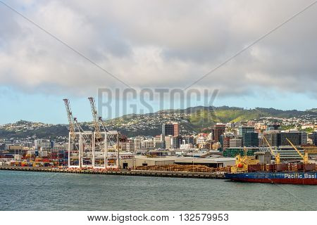 Wellington New Zealand - November 17 2014: Wellington cityscape capital city of New Zealand. Timber for export harbor crane and container crates on wharf of Wellington Harbour in New Zealand.