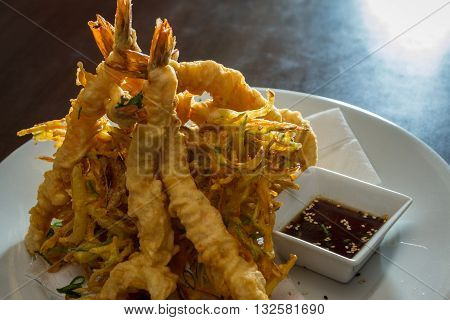close up of a dish with tempura fried shrimp and vegetables with a soy sauce dipping sauce