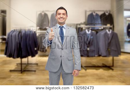 business, people, menswear, sale and clothes concept - happy smiling businessman in suit over clothing store background showing thumbs up