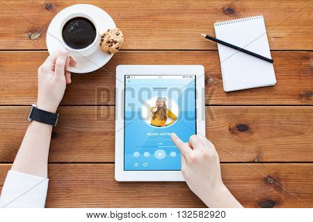 business, multimedia, technology and people concept - close up of woman with music player application on tablet pc computer screen, notebook and coffee on wooden table
