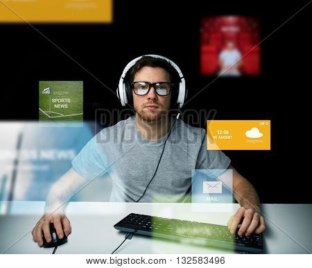 technology, communication, mass media, virtual reality and people concept - young man in headset and eyeglasses with pc computer keyboard over virtual screens