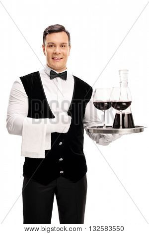Vertical shot of a cheerful waiter holding a tray with a bottle of red wine and two glasses isolated on white background
