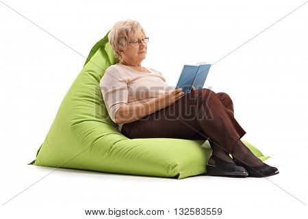 Mature lady reading a book seated on a comfortable green beanbag isolated on white background