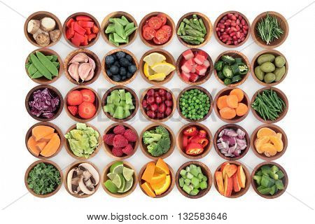 Paleolithic super health food of fruit and vegetables in wooden bowls over white wood background. High in vitamins, antioxidants, minerals and anthocyanins.