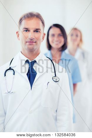 healthcare and medical concept - male doctor with stethoscope and colleagues