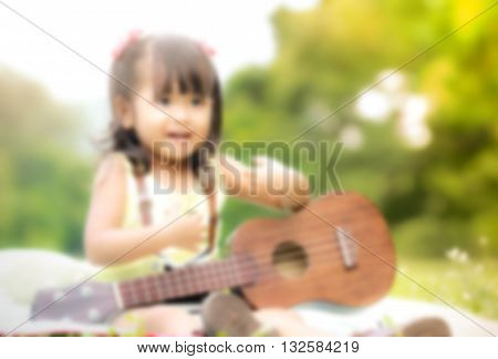 sweet dreamy and de-focused close up Asian little girl sitting on grass and play ukulele in garden