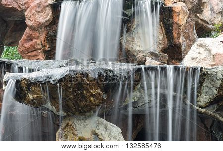 Waterfall flowing over rocks in the garden. Beautiful of waterfalls with soft flowing water and large colored rocks.( Blur blurred Waterfall)