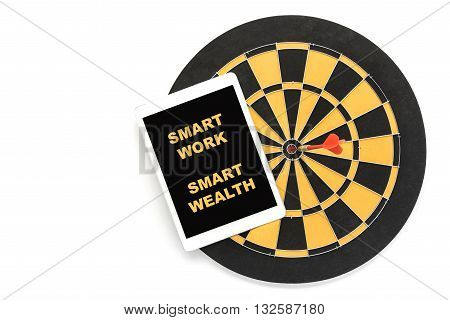 words smart work smart wealth on tablet screen over dart target on bullseye over white background with copy space Goal target success wealth business investment financial strategy education concept