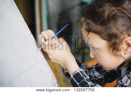 eight year old girl in a plaid shirt with enthusiasm that paints with a brush on canvas