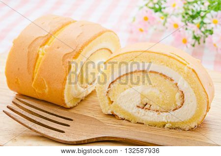 The Vanilla cake roll with flower on tablecloth.