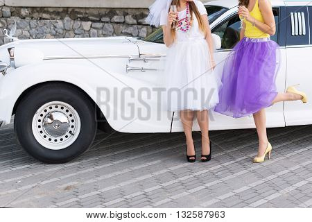 Group of girls celebrating a bachelorette party of bride. Celebration friends hen party concept - happy women with champagne glasses outdoors