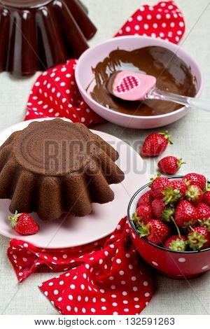 Chocolate cake. Decorating with chocolate icing and strawberries. Selective focus.
