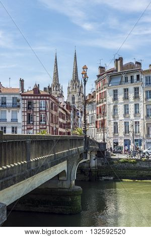 Bayonne France - May 21 2016: Pont Marengo bridge over Le Nive river with the Cathedral of Sainte-Marie de Bayonne in background. View from Quai des Corsaires. Aquitaine France.