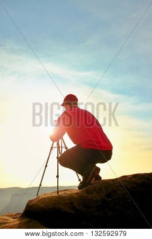 Photographerin Red Jacket And Red Baseball Cap  Stay With Camera On  Tripod On Cliff And Thinking. D