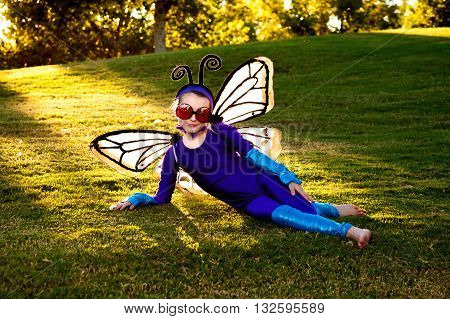 A young girl dressed in a home made butterfly costume reclines on a hillside in a park.