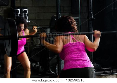 A strong female weightlifter does barbell squats with intense concentration. She is wearing a bright pink tank top and lipstick.