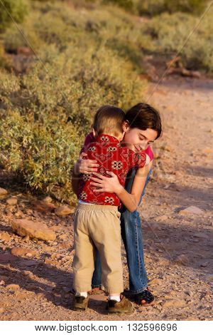 A big sister gives her little brother a comforting hug when he gets tired on a desert hiking trail. It is late afternoon and looks peaceful and sweet.