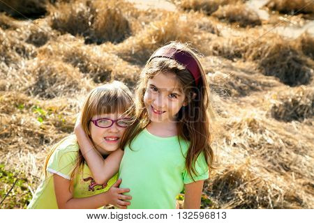Two sweet young sisters stand in a field of crushed dry reeds. The are hugging each other. The older has her hand wrapped around her younger sister's neck the younger has her arms around her older sister's waist.