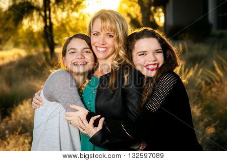 Two teen girls hug their mom. All three are beautiful and the scene is backlit.