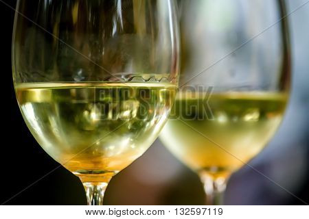 Two glasses of white wine with legs sit waiting to be enjoyed. Details include fingerprints and a bit of lint on the front glass.