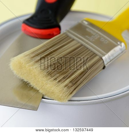 Paint brush with paint bucket and putty knife - home renovation concept