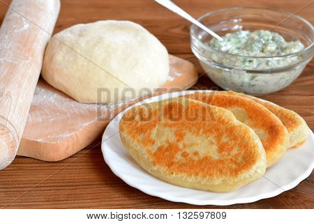 Fried pies on a plate. Dough and rolling pin on a cutting board. Cheese filling in a glass bowl. Wooden background. Home simply delicious food. Home cooking. Ingredients for making homemade pies