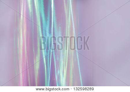 Ethereal iridescent background with streaks of pink, lilac, blue and other colors.