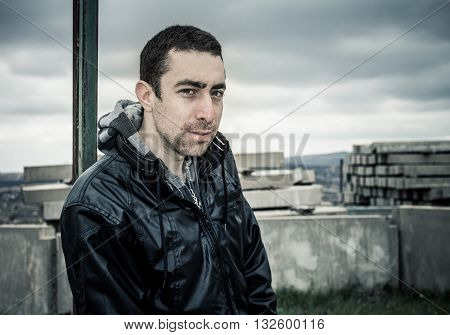 Man Looking At Camera With Sly Smile On His Serious Face