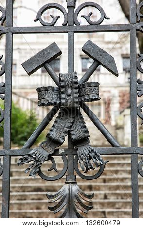 Symbol of the miners on the artistic forged gate. Coat of arms. Architectural element. Cultural heritage. Old symbolic place. Banska Stiavnica Slovak republic.