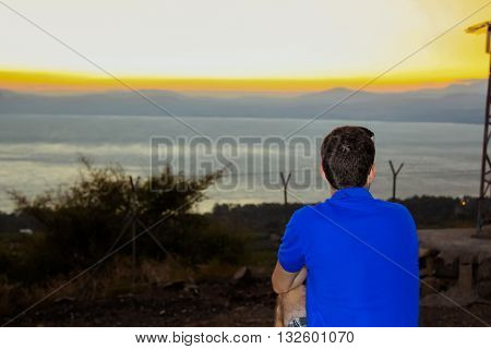 Back view of man watching the sunset at the Sea of Galilee.