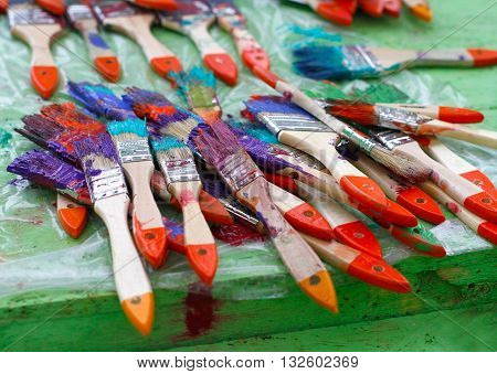 Dirty paintbrushes on cellophane on the table