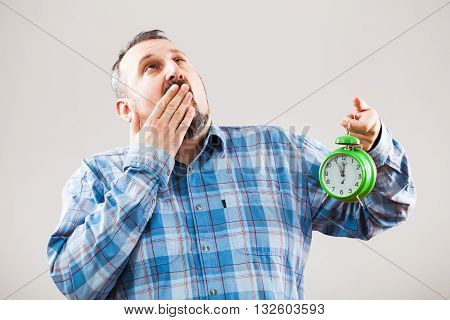 Studio shot portrait of tired man who is holding clock