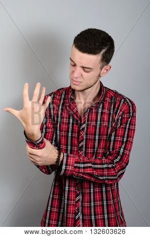 Man Holding Hand With Wrist Pain Over Gray Background