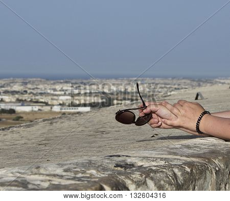 Woman keeping sunglasses in her hands with the panoramic view to Malta island, view from Mdina city, Malta, body part, conceptual photo of summer holidays