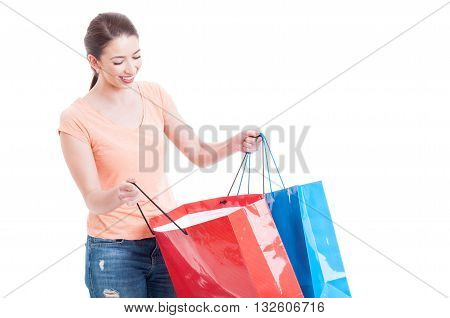 Smiling Woman Looking Inside Shopping Bags As Shopaholic Concept