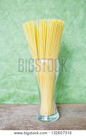 Line Spaghetti placed in a glass tumbler on a background of green nature.