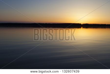 Sun going just behind the trees at a lake in Saskatchewan Canada