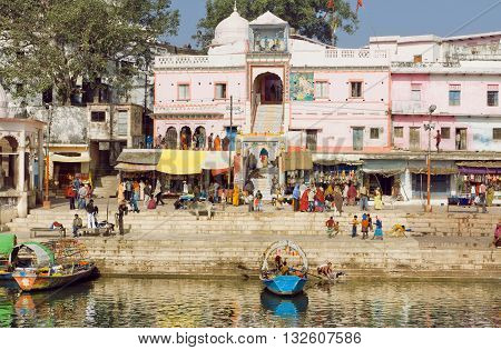 MADHYA PRADESH, INDIA - DEC 28, 2015: Old indian city buildings over the river with crowd of people outside on December 28, 2015 in Chitracoot. Population of Chitrakoot is 22294 people.