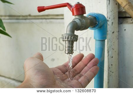 Rinsing a human hand with water from a tap