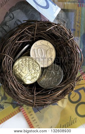Australian coins in a bird's nest with a background of notes.