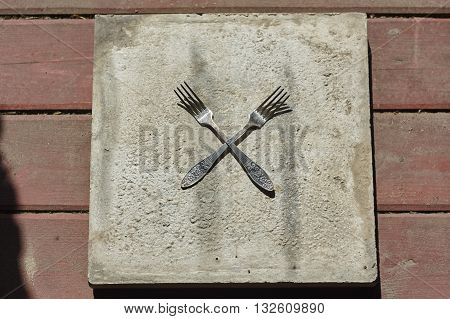 two crossed forks on concrete and wood floor