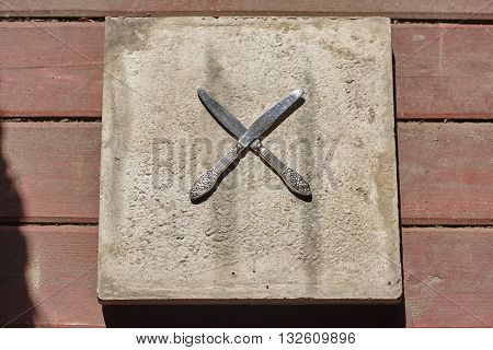 two crossed knives on concrete and wood floor