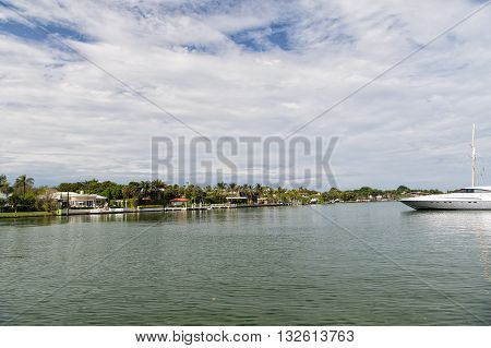 Beautiful landscape with boat on water coast with palms cloudy sky in summer or winter outdoor in Collins avenue South Beach Miami Florida