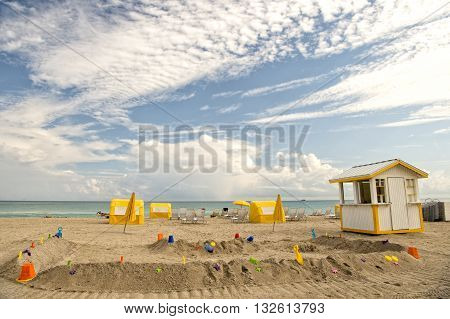 wooden lifeguard house on sandy beach with umbrellas chairs and toys on cloudy blue sky background south beach Miami USA